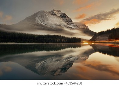 Mountain lake and traffic light trail with reflection and fog at sunset in Banff National Park, Canada.