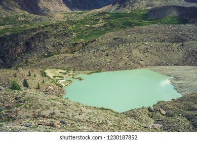 Mountain lake in valley of highlands. Giant mountainside with vegetation. Amazing rocks. Wonderful mountains. Smooth water surface. Atmospheric cosmic landscape of majestic nature.