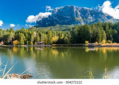 mountain lake view in autumn with colorful trees that are reflected on the clear waters of the dolomites