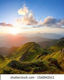 Mountain landscape with beautiful sunrise, cloudy sky and orange colorful horizon. Spring sunny morning. Wallpaper background. Touristic place Maramures, Carpathian, Ukraine, Europe.