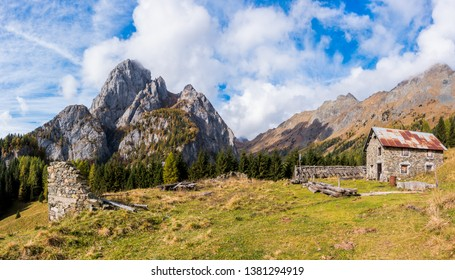 Mountain landscape with blue sky with clouds and ruins of an old farm
