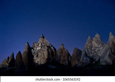 Mountain landscape in Cappadocia at night, fairy chimneys with stars, Turkey