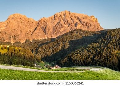 Mountain landscape during sunset in the Dolomites in South Tyrol: mountain peaks lit by sunset, sinuous road on white flower meadow in a valley