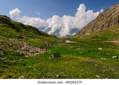 Mountain landscape in green valley with small lake and colouds, Caucasian mountains.