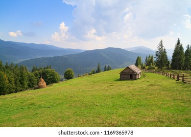 Mountain landscape with haystacks. Agricultural field in mountain area. beautiful countryside landscape