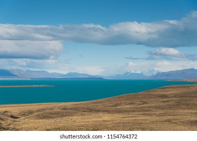 mountain landscape with lake, blue sky, and dry land, Patagonia, Argentina