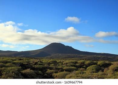Mountain Landscape. Lanzarote, Canarias Island. Cueva de Ls Verdes, Jameos del Agua, Mirador del Rio, Costa Teguise, Timanfaya National Park, Volcano. Daylight, blue sky, small white clouds.