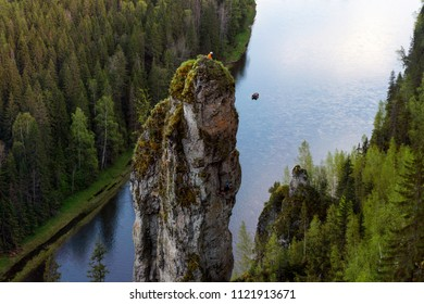 Mountain landscape of the Middle Urals with the rock Devil's Finger on the river Usva; сlimbers on top of the cliff and raft with tourists on the river are seen