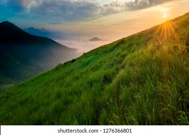 Mountain landscape in nice weather at sunrise. Green grassy steep hill, foggy valley and distant mountains under bright blue sky with lit by raising sun white clouds. Beauty of nature concept.