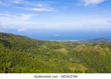 Mountain landscape on the island Camiguin, Philippines. Thick rainforest on the hills in sunny weather. Big tropical island with volcanoes.
