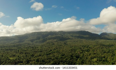 Mountain landscape on tropical island with mountain peaks covered with forest from above. Mountains covered rainforest, trees and blue sky with clouds, aerial view. Camiguin, Philippines. Slopes of