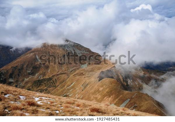 Mountain landscape. Panoramic view from Bystrá peak on Klin peak. Autumn colored mountains with snow. Western Tatras, High Tatras national park, Slovakia.