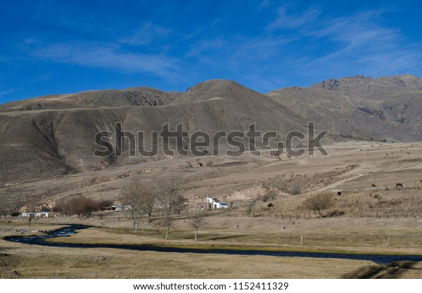 mountain landscape with river that goes to the arid valley