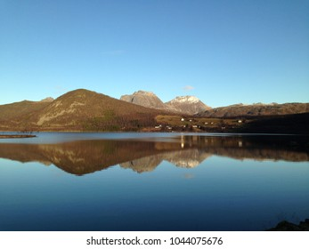 Mountain landscape with rural settlement and water reflection
