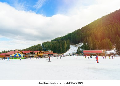 Mountain landscape. Ski resort, Bansko, Bulgaria. Ski track. People ski on snow in the winter. Pine forest