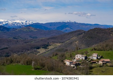 Mountain landscape with a small village meadows, forest and snow-capped peak in Ariege, french Pyrenees,