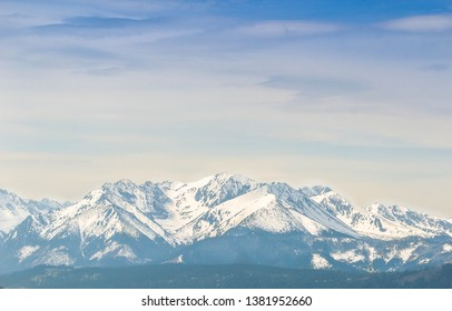 Mountain landscape of the snowy peaks under the blue cloudy sky