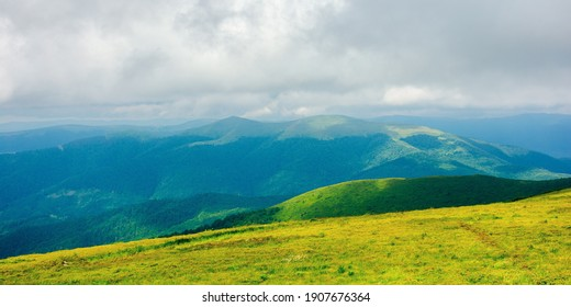 mountain landscape in summer on a cloudy day. grass covered hillside meadow. carpathian watershed ridge in the distance