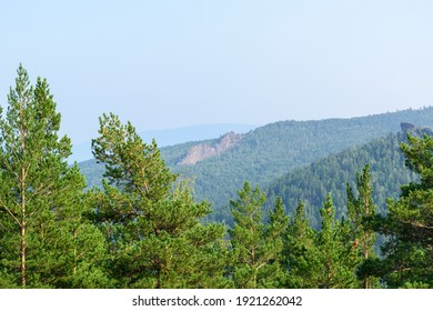Mountain landscape in summer. Pine forest with green needles. Mountain slope with a rock. The sky is hazy. Summer tourism concept. - Shutterstock ID 1921262042