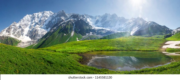 Mountain landscape of Svaneti on bright summer sunny day. Mountain lake, hills covered green grass on snowy rocky mountains background. Caucasus peaks in Georgia. Amazing view on wild georgian nature