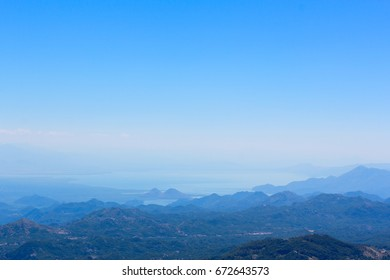 Mountain landscape and the tops of mountains in blue fog and with a clear sky.