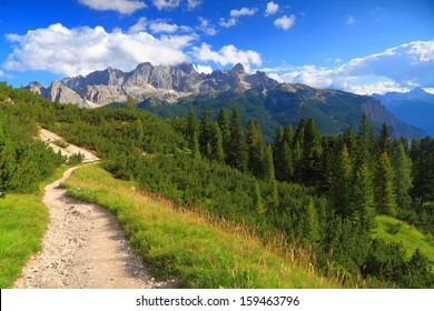Mountain landscape with trail and green meadow and forest, Dolomite Alps, Italy