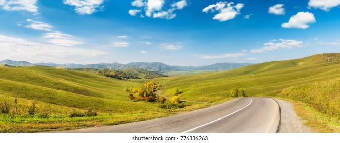 Mountain Landscape under Blue Sky with an Asphalt Road