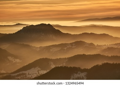 Mountain landscape with winter fog at sunset