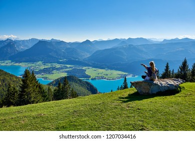 Mountain landscape with woman, dog, lake and forest in Austrian Alps. Salzkammergut region, Wolfgangsee
