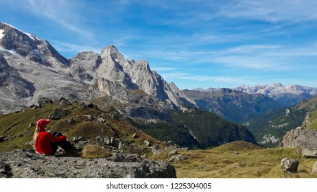 Mountain landscape. Young woman trekker looking at Marmolada mountain range, Passo Pordoi, Dolomites Mountain, Italy
