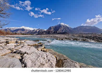 Mountain landscape,with river rocks and waterfall against blue sky.