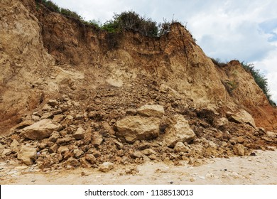 Mountain landslide in an environmentally hazardous area. Large cracks in earth, descent of large layers of earth blocking road. Mortal danger of dam at foot of landslide slopes of mountain