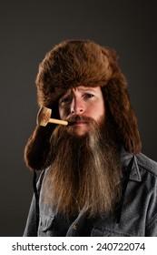 Mountain man wearing a fur hat and smoking a corn cob pipe