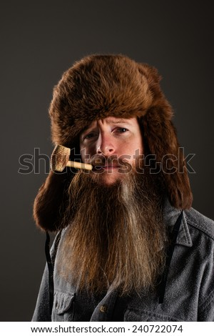 Mountain man wearing a fur hat and smoking a corn cob pipe