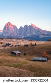Mountain meadow and house Alpe di Siusi or Seiser Alm in the background Langkofel mountain range at sunset with Province of Bolzano, South Tyrol in Dolomites at Italy