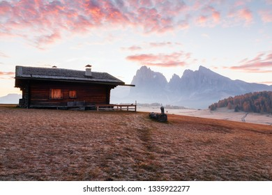 Mountain meadow and house Alpe di Siusi or Seiser Alm in the background Langkofel mountain range at sunrise with Province of Bolzano, South Tyrol in Dolomites at Italy