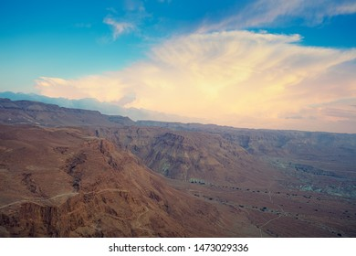 Mountain nature landscape. View of valley from mount. Desert in early morning. Beautiful sunrise over Masada fortress with dramatic sky. Judaean Desert. Landscape in Dead sea region. Nature Israel.