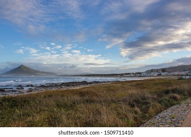 Mountain on ocean coast in the morning. Scenic landscape near Caminha, Portugal. Panoramic seascape with stones in water and green hill on horizon. Camino de Santiago landscape.