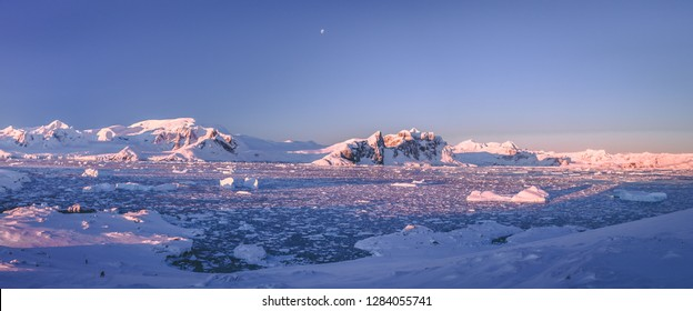 Mountain panorama of Antarctica shoreline. Amazing panoramic view. The pieces of the ice floating in the frozen ocean. Breathtaking winter landscape in the blue tints. Travel, nature, destination