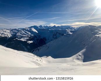 Mountain panorama of the Austrian ski resort of Saalbach-Hinterglemm , Austria with beautiful sunlight against a great blue sky.