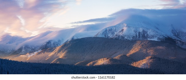 Mountain panorama with beautiful clouds and sunset. Winter landscape with a peak