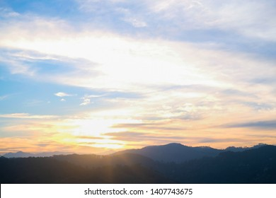 Mountain panorama from a bird's eye view. The sky above the mountain peaks at sunset. Bright multi-colored clouds, the sun's rays pass through the air and make orange, yellow, pink reflexes