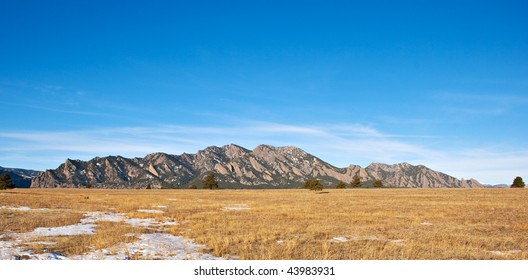 Mountain panorama with golden grassy field in winter in the Colorado prairie near Boulder