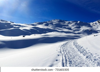 Mountain panorama with snow, sun and snowshoe trail in winter in Stubai Alps, Austria