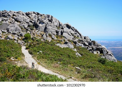 Mountain path leading to large rocks with across the Monchique mountains and countryside, Foia, Algarve, Portugal, Europe.
