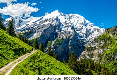 Mountain path to snow topped peak landscape - Shutterstock ID 1850130346