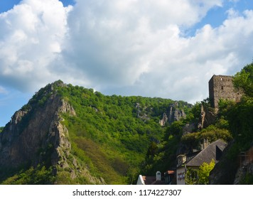 A mountain peak is covered with forest. Ruins of a castle can just be seen. Below are the rooftops of the village. The sky is overcast.