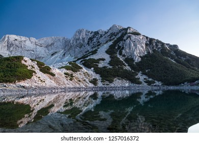 Mountain peak reflected in the water of the lake at sunset