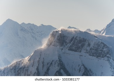 Mountain peak with a lot of snow and heavy winds creating dangerous snow drifts proon to avalanches in the Swiss alps with mountains in the background and sunshine