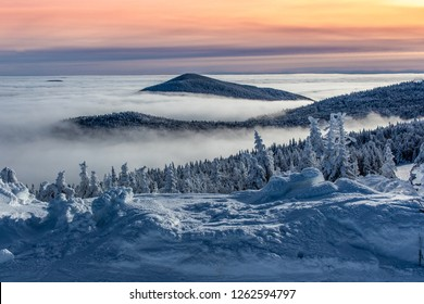Mountain peaking through cloud inversion during sunset orange sky in the Green Mountains of Vermont.